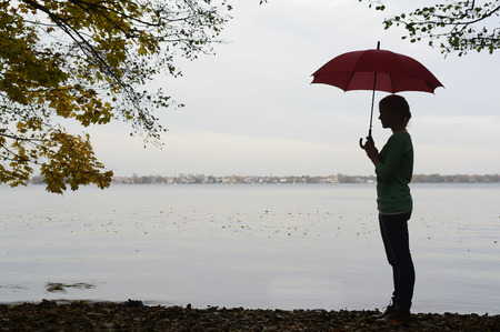 autumnally: Germany, Berlin, Mueggelsee, young woman with umbrella by the lake Stock Photo