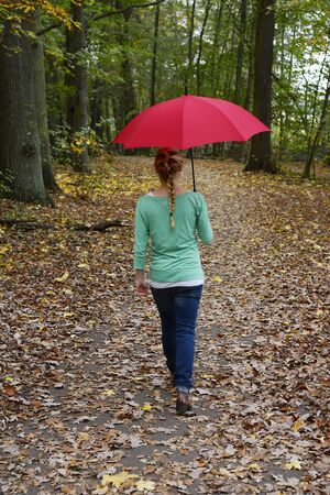 Germany, Berlin, young woman with red umbrella in forest photo