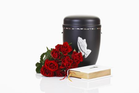 Begrafenis, urn met het bidden handen, wit bijbel en rode rozen Stockfoto