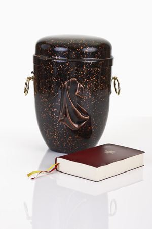 decease: Urn and bible on white background Stock Photo