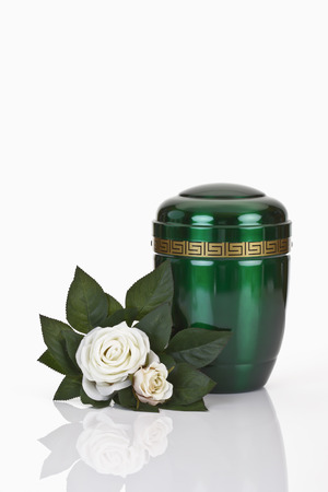 decease: Green urn and white roses on white background Stock Photo