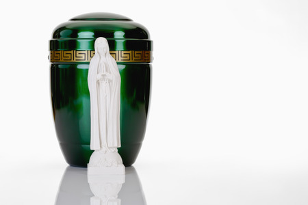 decease: Green urn and saint figure on white background Stock Photo