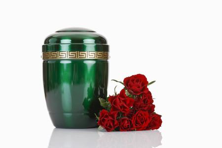luto: Urna y rosas rojas verdes sobre fondo blanco Foto de archivo