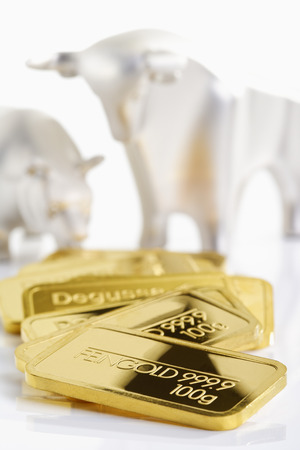 affluence: Gold bars in front of bull and bear Stock Photo