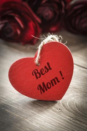 agradecimiento: Ranúnculos con el corazón rojo en la madera, mejor mamá