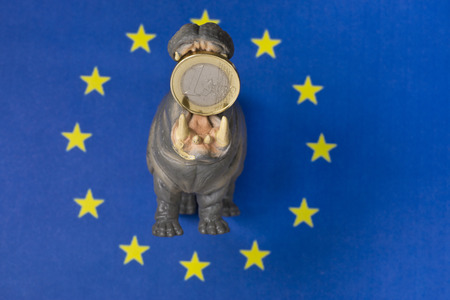 swallowing: One euro coin in mouth of hippo figurine, Europe flag