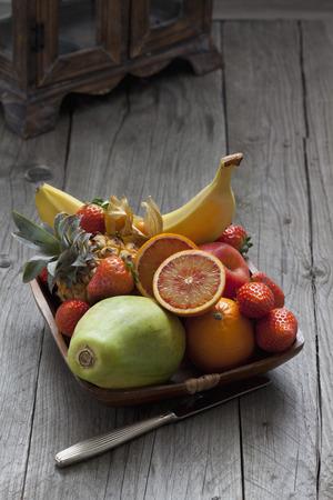 fruit bowl: Fruit bowl with fruits, knife on wood Stock Photo