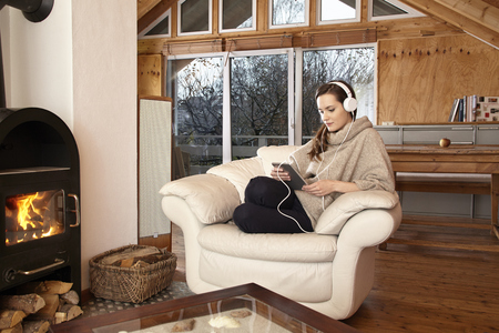 head phones: Young woman at home in chair with tablet and head phones Stock Photo