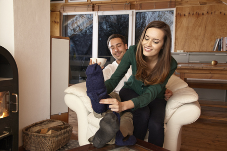 Man sitting in armchair, woman removing his socks