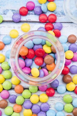 smarties: Colorful smarties, glass, wood