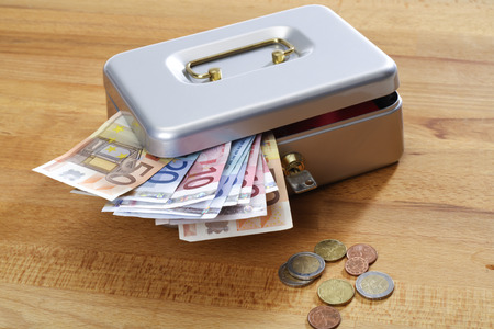 cash box: Cash box with euro notes and coins on wood Stock Photo