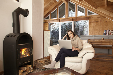 fireplace living room: Young woman at home in chair Stock Photo