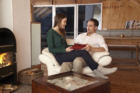 gifting: Happy couple at home, man gifting woman with present