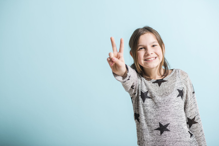 victory sign: happy young girl showing victory sign