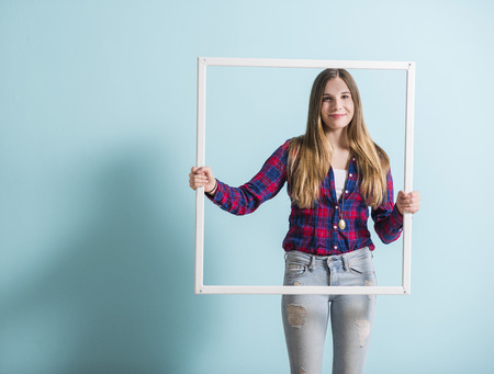 Young girl looking through picture frame