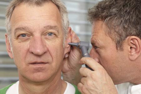 Oudere man op medisch onderzoek, otoscopie Stockfoto