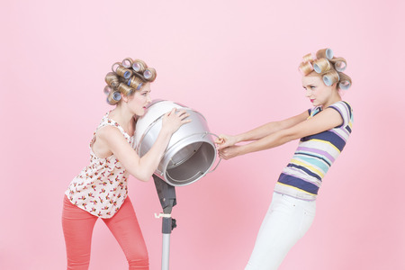 catfight: Young woman with curlers, quarreling about hood drier