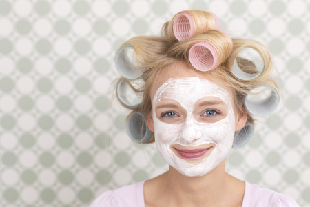 cremas faciales: Joven con rulos y mascarilla, sonriendo