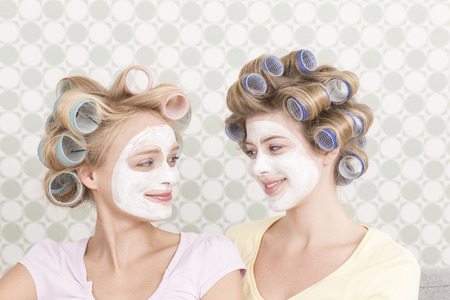 cremas faciales: Las mujeres jóvenes con rulos y mascarilla Foto de archivo