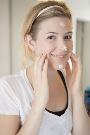 Young woman creaming her face Standard-Bild