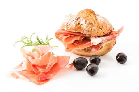 parma ham: Parma ham, bread roll and black olives Stock Photo