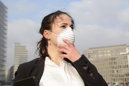 contaminacion aire: Mujer de negocios usando máscara de protección contra la contaminación, Berlín, Alemania
