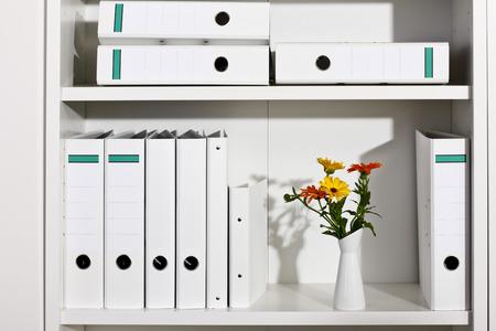 organized office: Shelf with white folders and flower vase