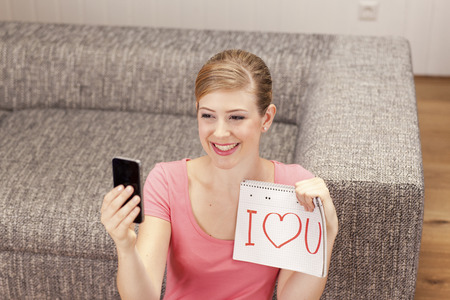 egocentric: Young woman making selfie, I love you on notepad, smiling