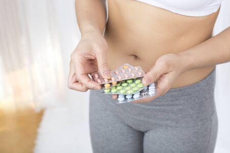 diarrhoea: Young woman holding tablets, belly Stock Photo