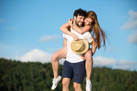 man carrying woman: Young couple, man carrying woman piggyback Stock Photo