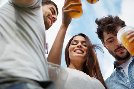 funny glasses: Group of friends toasting with beer in plastic glasses Stock Photo