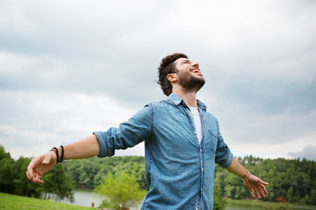 Emotional young man laughing in wind Stock Photo