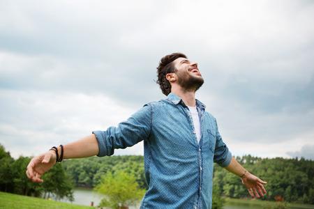 Emotionele jonge man lachen in de wind