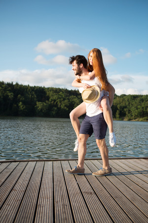 carrying girlfriend: Young couple at lake, man carrying girlfriend piggyback