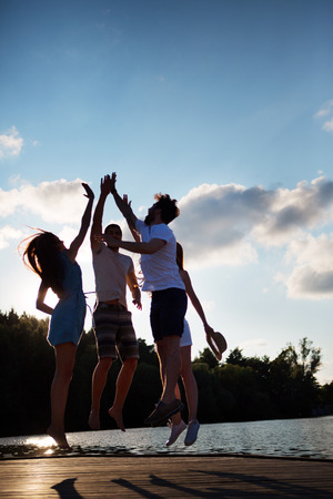 high society: Group of friends jumping on jetty giving high five
