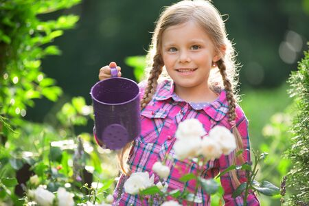 twee: Girl watering flowers in garden with watering can