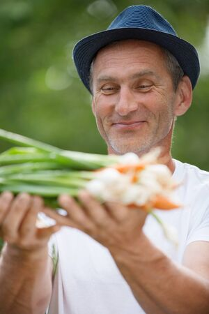spring onions: Man with hat holding freshly harvested carrots and spring onions Stock Photo
