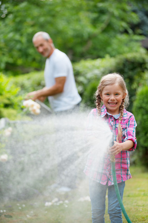 watering the plants: Father and daughter watering plants in garden