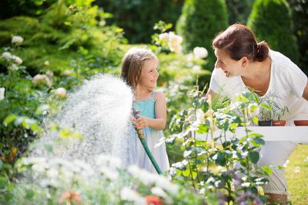 manguera: Ni�a y abuela regando flores en el jard�n Foto de archivo