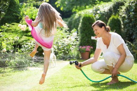 Grandmother watering garden , girl jumping over water jet