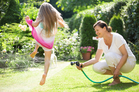 kids playing water: Grandmother watering garden , girl jumping over water jet