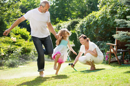 woman gardening: Girl and grandparents playing and waterin garden Stock Photo