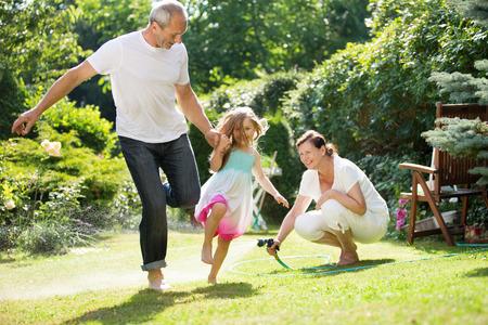 Niña y sus abuelos que juegan y waterin jardín