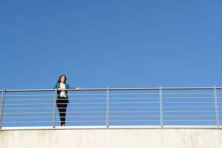 businesswoman standing: Businesswoman standing on bridge Stock Photo