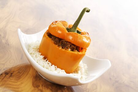 mincemeat: Orange bell pepper stuffed with mincemeat on rice and plate Stock Photo