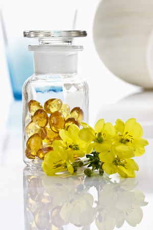 Blossoms and apothecary flask with evening primrose oil capsules