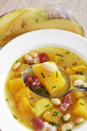 swede: Swede soup with white beans and bacon, spoon and plate Stock Photo