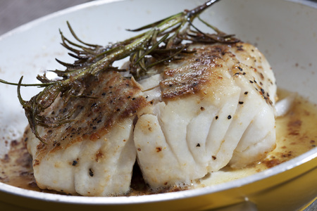 Fried coalfish fillet with rosemary in pan photo
