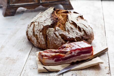 Farmhouse bread and bacon on jute on wood Stock Photo