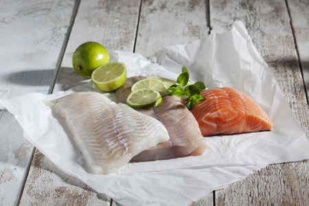 haddock: Fish fillets, haddock, coalfish and salmon, limes and herbs on greaseproof paper, wood